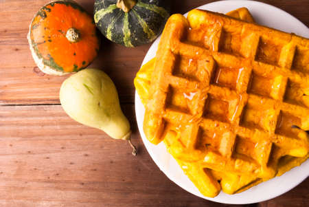 Freshly baked homemade Belgian waffles with pumpkin. On a wooden table with decorative pumpkins and honey, Top view, copy space