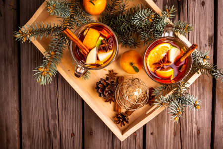 Christmas mulled wine with the addition of fragrant spices, apples, mandarins and oranges, top view, in a tray, on wooden table. With Christmas tree branches and pine cones Stock Photo