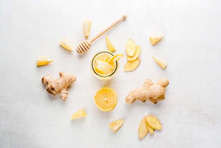 Imbir napój cytrynowy w butelce ze słomką. Wybór składników koktajlu lub herbata imbir: imbiru, cytryny, miód. Na białym stole. Widok z góry, kopia przestrzeń