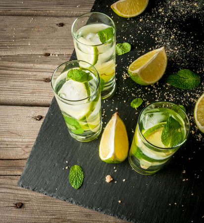 daiquiri alcohol: Refreshing lime mojito or tequila with ingredients for it - lime, mint, brown cane sugar. Close view Stock Photo