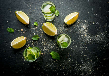 Refreshing lime mojito or tequila with ingredients for it - lime, mint, brown cane sugar. Close view Reklamní fotografie