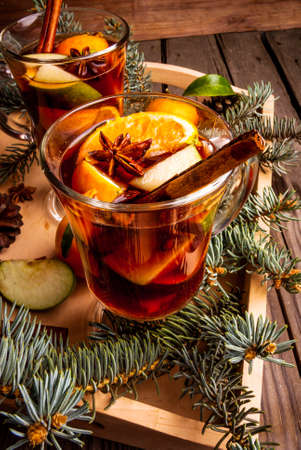 dcor: Christmas mulled wine with the addition of fragrant spices, apples, mandarins and oranges. With Christmas tree branches and pine cones. Stock Photo