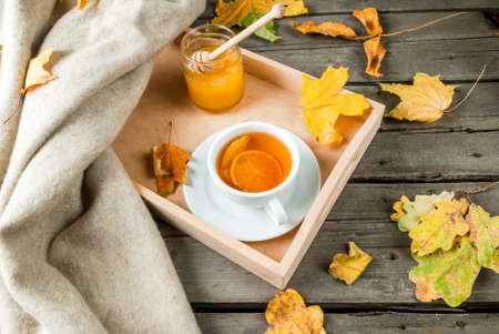 Cozy autumnal mood, warm autumn. A cup of hot tea with lemon and ginger on a rustic table, plaid, yellow leaves, honey and a book to read.