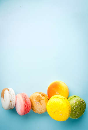 Multicolored macaroon cookies with on a blue background, top view, copy space Stock Photo
