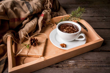 Hot chocolate mug and christmas present on rustic table with blanket or plaid, cozy and tasty breakfast or snack