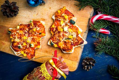 Grappige Kerstmis maaltijd voor kinderen: pizza in de vorm van kerstbomen, groenten en kaas. Stockfoto