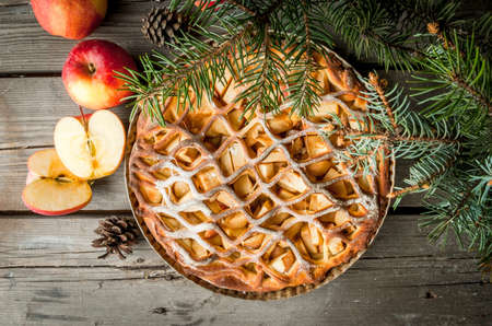 dollop: Traditional american apple pie on rustic wooden table, with apple. Near the Christmas tree branches and pine cones, top view, copy space Stock Photo