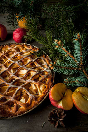 Traditional american apple pie on rustic wooden table, with apple. Near the Christmas tree branches and pine cones, top view, copy space Stock Photo