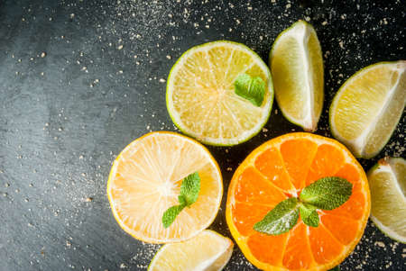 Fresh citrus fruits on a black slate table - tangerine, lime, lemon, mint leaves and brown cane sugar. Top view, copy space