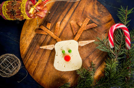 Funny Christmas breakfast, a sandwich for a child in the form of the muzzle of the deer (cheese, bread, vegetables), With branches of Christmas trees and decorations, top view, copy space Stock Photo