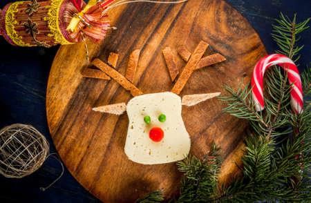 prima colazione di Natale divertente, un panino per un bambino nella forma del muso del cervo (formaggi, pane, verdure), con rami di alberi e decorazioni di Natale, vista dall'alto, copia spazio Archivio Fotografico