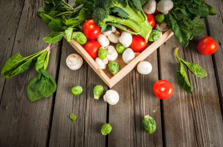 Fresh raw organic vegetables on a rustic wooden table in basket: spinach, broccoli, Brussels sprouts, tomatoes, mushrooms, champignons. Stock Photo