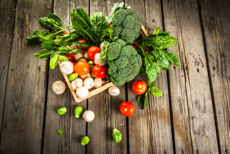 Fresh raw organic vegetables on a rustic wooden table in basket: spinach, broccoli, Brussels sprouts, tomatoes, mushrooms, champignons. Stockfoto