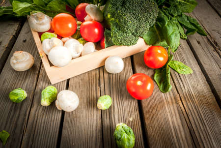 brussels sprouts: Fresh raw organic vegetables on a rustic wooden table in basket: spinach, broccoli, Brussels sprouts, tomatoes, mushrooms, champignons. Stock Photo