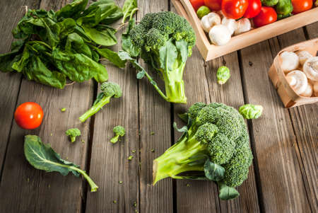 broccoli sprouts: Fresh raw organic vegetables on a rustic wooden table in basket: spinach, broccoli, Brussels sprouts, tomatoes, mushrooms, champignons. Stock Photo
