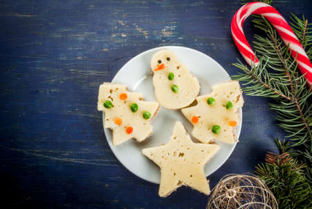 sandwitch: Funny Christmas breakfast, sandwiches in the form of Christmas trees, reindeer and snowmen. With branches of Christmas trees and decorations, top view Stock Photo