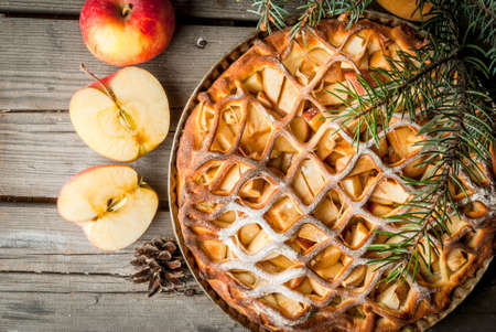 Traditional american apple pie on rustic wooden table, with apple. Near the Christmas tree branches and pine cones, top view