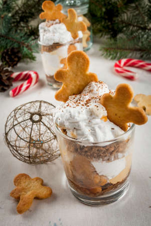 x mass: Christmas dessert, funny food for children or party. Ginger Trifle with gingerbread in form of men, diving in the drifts of whipped cream. Stock Photo