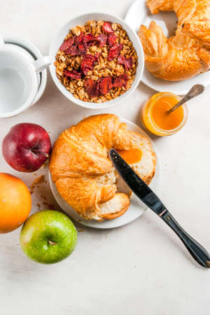 apples and oranges: Everything you need for easy and a wholesome breakfast: croissants, jam, granola, oatmeal and dried fruit, fresh fruit (apples, oranges), a cup of tea or coffee