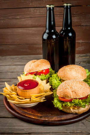 nibbles: Selection of different food for a party: chips, nachos with sauces (tomato, cheese and mayonnaise tartar), burgers and beer, copy space Stock Photo