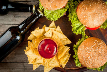 Selection of different food for a party: chips, nachos with sauces (tomato, cheese and mayonnaise tartar), burgers and beer, copy space, top view