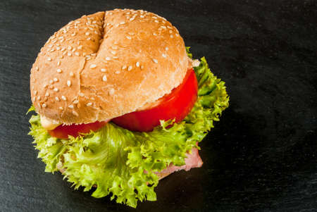 freshly prepared: Freshly prepared homemade burger: a bun with sesame seeds, meat, cheese, lettuce, tomato and cheese sauce, copy space