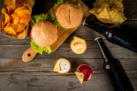 themed: Selection of different food for a party: chips, nachos with sauces (tomato, cheese and mayonnaise tartar), burgers and beer, copy space, top view