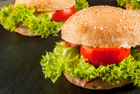 freshly prepared: Freshly prepared homemade burgers: a bun with sesame seeds, meat, cheese, lettuce, tomato and cheese sauce, close view, copy space Stock Photo