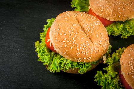 freshly prepared: Freshly prepared homemade burgers: a bun with sesame seeds, meat, cheese, lettuce, tomato and cheese sauce, copy space