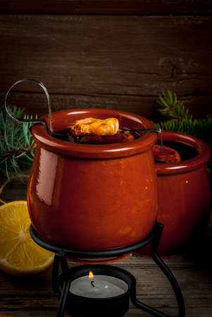 wood burner: Traditional German Christmas drink Feuerzangenbowle, analogue of mulled wine: hot wine with orange, lemon and spices, complemented by burning sugar and rum Stock Photo