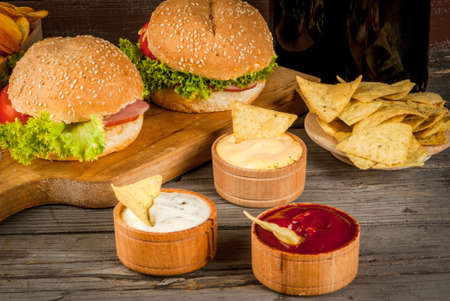 Selection of different food for a party: chips, nachos with sauces (tomato, cheese and mayonnaise tartar), burgers and beer, copy space Stock Photo