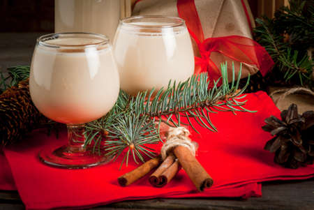 Traditional Christmas alcoholic cocktail - Irish Cream, Cola de mono (monkey tail), decorated with cinnamon. Against the background of Christmas decorations on a wooden table. Copy space Stock Photo