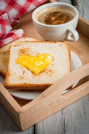 Idea for the celebration of Valentines day: breakfast - toast with scrambled eggs in the form of hearts, sausages and cheese in the form of hearts and aromatic coffee with cinnamon, copy space, close view