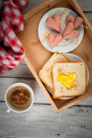 bacon love: Idea for the celebration of Valentines day: breakfast - toast with scrambled eggs in the form of hearts, sausages and cheese in the form of hearts and aromatic coffee with cinnamon, copy space top view