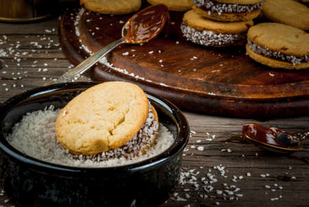 Cooking alfajores - a traditional dessert from Latin America or Mexico. Shortbread cookies with dulce de leche and coconut. Stock Photo