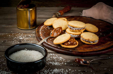 alfajores: Cooking alfajores - a traditional dessert from Latin America or Mexico. Shortbread cookies with dulce de leche and coconut. Stock Photo