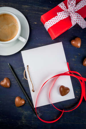 card making: Preparations for Valentines Day: a notebook for congratulation or sweet notes, gift, candy in the form of hearts, red ribbon and a cup of coffee, top view, copy space
