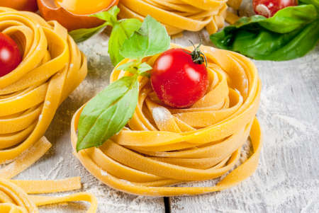 Home made raw uncooked pasta, with basil leaves, scented oil and cherry tomatoes. On a white rustic wooden table, copy space Stock Photo