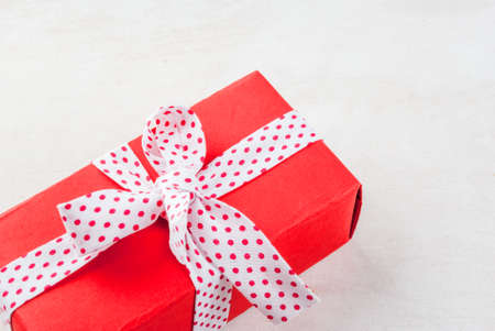 tied in: Background, valentines day. Gift in red paper, tied with a festive ribbon Stock Photo