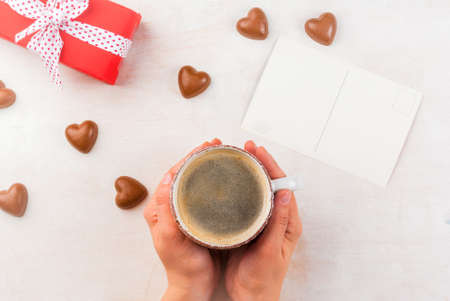 Concept for the celebration of Valentines flavored coffee, candy heart shaped gift in red paper with ribbon and card. Space for text or congratulations. Hands in the frame, the girl holds coffee mug