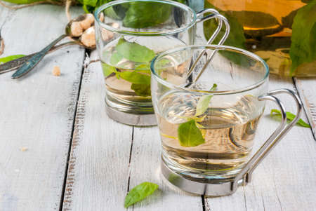 Basil herbal tea in a transparent cup and teapot, spoon with cane sugar, a bunch of fresh basil. On a white wooden table. Copy space Stock Photo