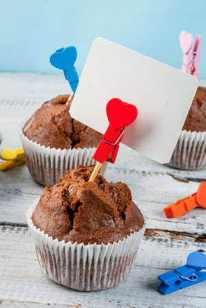 Chocolate muffins for Valentines Day; clothespins decorated with the image of heart and a card for greetings or notes, copy space