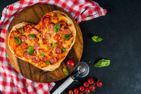 Idea for the celebration of Valentine's Day: pizza for two persons in the shape of heart Stockfoto