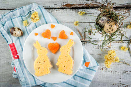 Cute and funny breakfast for Valentine's Day or Easter: sandwiches in the form of bunnies, hearts supplemented carrot and quail eggs.