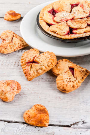 Idea for the celebration of Valentines Day: big cherry pie and one-bite  cherry pies in the form of hearts, cup of coffee