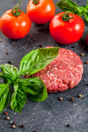 Fresh raw home-made minced beef steak burger with spices, tomatoes and basil, on a stone table, copy space, close view