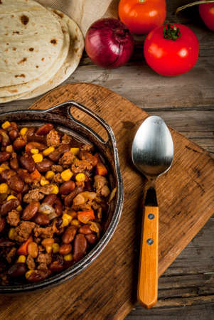 Traditional Mexican and Chilean dish of chilli con carne. In the rustic pan, next to tortillas and fresh vegetables on a wooden table, top view, copy space Stock Photo