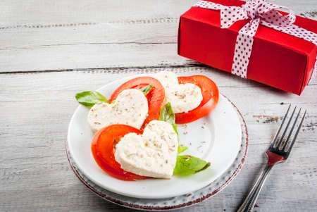 Idea for the celebration of Valentines Day: a light lunch or snack - salad with tomatoes and cheese, cut in the shape of heart. On wooden table with gift. copy space Stockfoto
