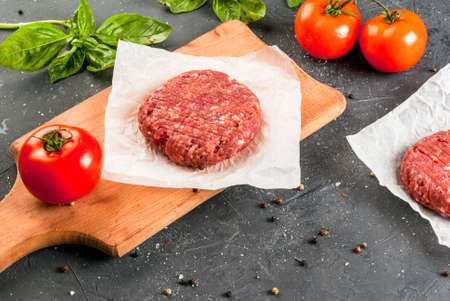 Fresh raw home-made minced beef steak burger with spices, basil and tomatoes on a cutting board on a stone table, copy space, top view