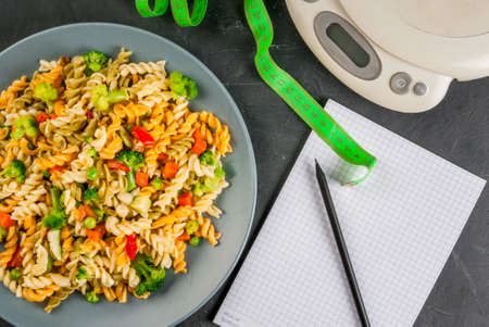 Concept of dieting, counting calories: a plate of healthy food (whole grain pasta with vegetables), scales for weighing food, tape measure, notepad and pencil for a food diary, top view, copy space Stock Photo